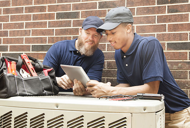 Two men working on an AC using tablet with Business Manager 365