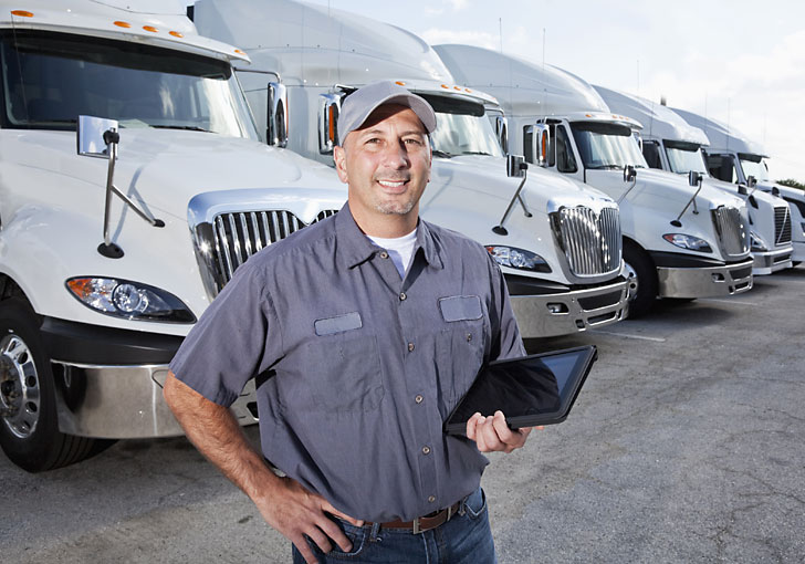 Truck driver holding laptop using business manager 365